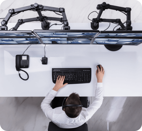 Elevated View Of Male Security Guard Monitoring Multiple Camera Footage On Computer At Workplace