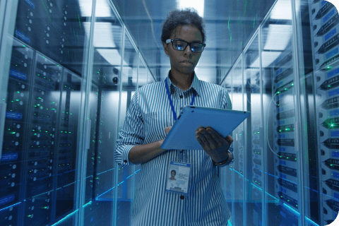 person in a server room with a tablet